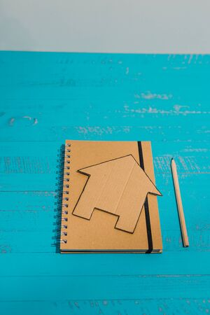notebook with house made of cardboard next to it, concept of writing down renovation tasks or budgeting for a mortgage