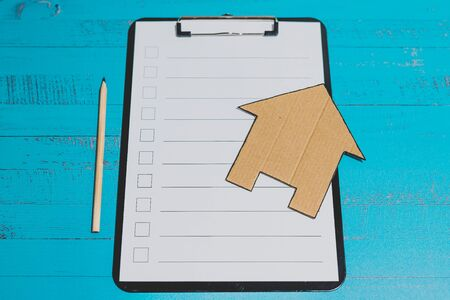 clipping board with blank list with cases to tick and cardboard house miniature on top of it, concept of planning a renovation or tasks to move house 版權商用圖片