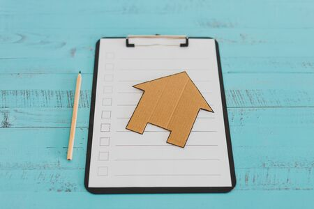 renovation or mortgage themed blank checklist with miniature house on clipboard 免版税图像