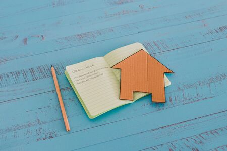 green home checklist, miniature house on notepad with sustainable elements for environmentally conscious property Archivio Fotografico