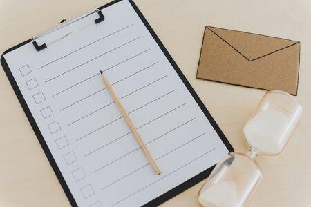Posteingangs-Stress-Konzept, E-Mail-Miniatur neben leerer Checkliste mit Sanduhr auf dem Schreibtisch Standard-Bild