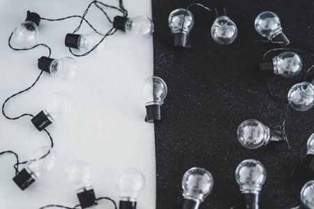 unkonventionelles Ideenkonzept, einzigartige Glühbirnenkugel mittig im Rahmen, die sich unter anderem auf schwarz-weißem kontrastierendem Hintergrund abhebt