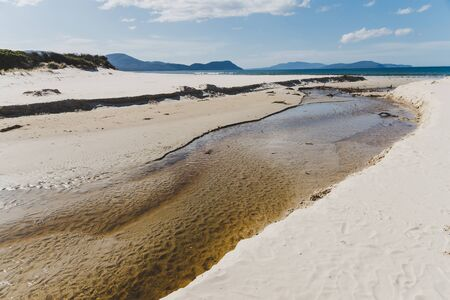river estuary across the beach meeting the South Pacific Ocean in Marion Bay along the East Coast of Tasmania Australia