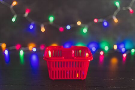 festive season shopping concept, shopping basket with multicolour Christmas string lights bokeh in the background
