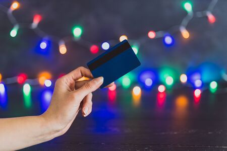 festive season shopping concept, hand holding payment card with multicolour Christmas string lights bokeh in the background