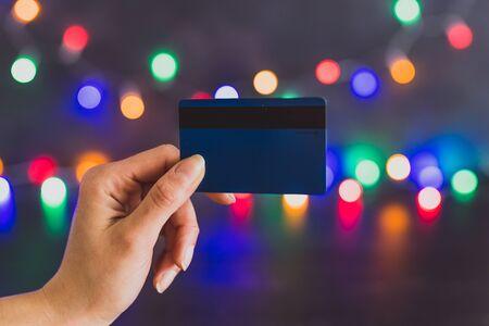 Concepto de compras de temporada festiva, mano sujetando la tarjeta de pago con luces de cadena de Navidad multicolores bokeh en el fondo