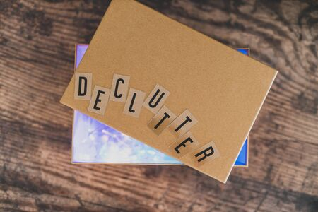 tidying up and sorting your possessions concept, declutter message on top of semi-open box to fill with items to give away (version with lights shining from inside the box) Stock Photo
