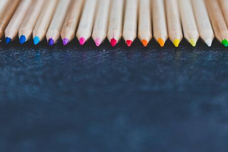coloured pencils lined up on dark desk in color gradient order with copyspace, close-up version