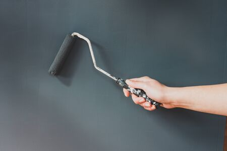 woman's hand holding paintbrush roller with muted cold grey tone against matching wall, concept of finishing touches or last coat of home renovation jobs