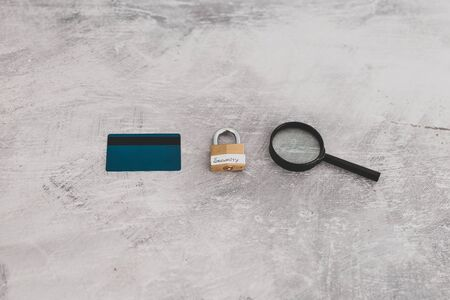 buyer protection and sensitive data online, credit card with security lock and magnifying glass on light concrete background