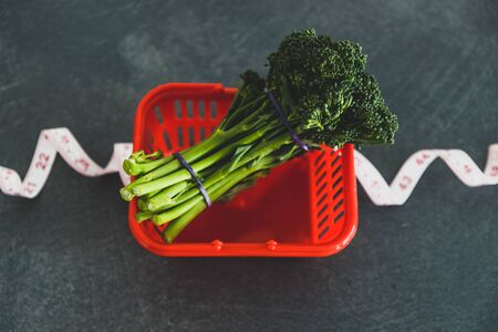 eating healthy and dieting concept, groceries shopping basket wrapped up with measuring tape next to bunch of broccolini