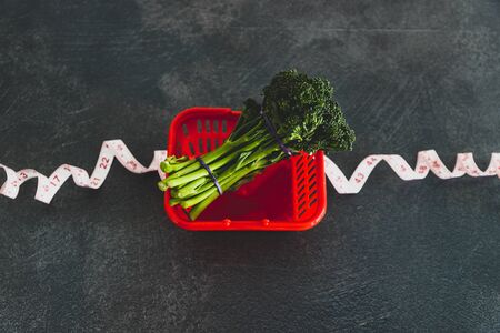 eating healthy and dieting concept, groceries shopping basket wrapped up with measuring tape next to bunch of broccolini 写真素材
