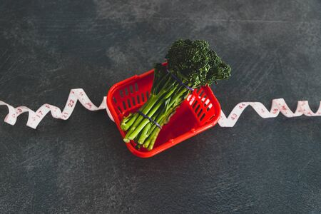 eating healthy and dieting concept, groceries shopping basket wrapped up with measuring tape next to bunch of broccolini Banco de Imagens