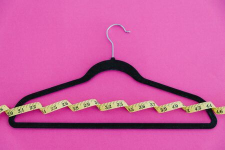 concept of fashion imposing trends of losing weight to fit small sizes, clothes hanger with measuring tape on pink background
