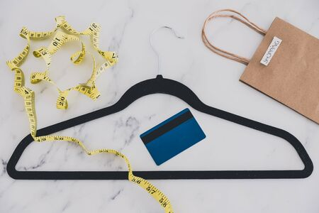 concept of expensive bespoke tailored fashion, clothes hanger with measuring tape with shopping bag and payment card