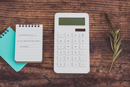 Companys Environmental Impact message on notead next to calculator and dry leaves, concept of ecology and corporate actions