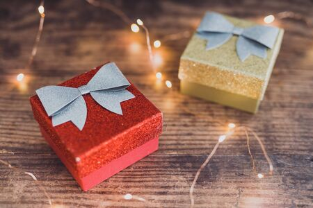 Christmas present box with bow and glitters surrounded by fairy lights, concept of gift giving and seasonal holiday shopping