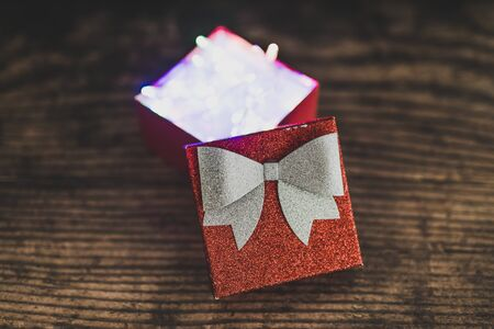 Christmas present box with shining fairy lights inside, concept of gift giving and seasonal holiday shopping