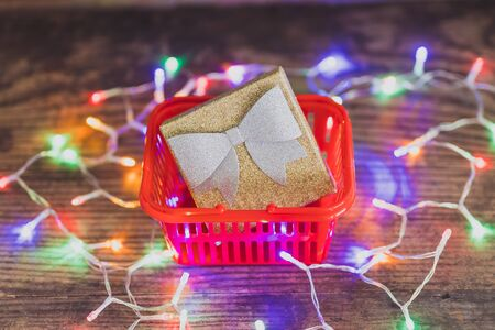 Christmas present box with bow and glitters inside shopping basket surrounded by colorful festive fairy lights, concept of gift giving and seasonal holiday shopping 版權商用圖片