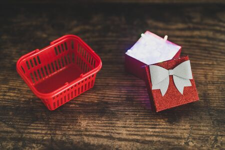 Christmas present box with shining fairy lights inside next to shopping basket, concept of gift giving and seasonal holiday shopping