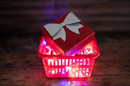 Christmas present box with bow and glitters inside shopping basket with colorful festive fairy lights inside of it, concept of gift giving and seasonal holiday shopping 版權商用圖片