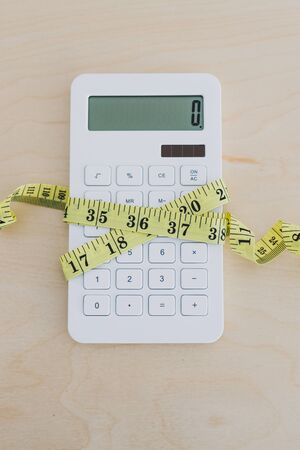 concept of tightening up your budget or expenses, calculator wrapped up by measuring tape Stockfoto