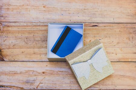 payment card or gift card inside open present box on wooden table, concept of shopping and celebrations