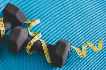 weightloss and exercise concet, fitness dumbbell set on yoga mat with measuring tape wrapped around them Banco de Imagens