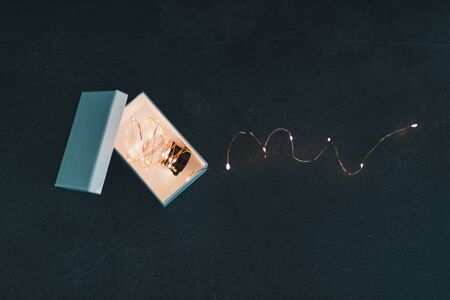concept of inventiveness and thinking outside the box, idea lightbulb wrapped up in string lights shining from open box