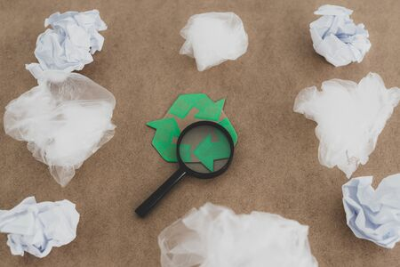 ecology and single-use plastic pollution concept, group of plastic bags with green recycle symbol and magnifying glass analyzing the materials Stock Photo