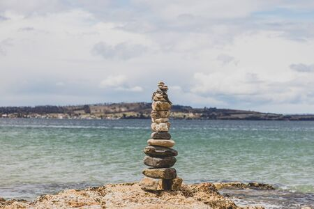 pebbles and rocks in zen inspiring stack on the shore in Australia with soft morning light and relaxing beach landscape bokeh