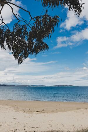 pristine Australian coastline and beach landscape with blue Pacific Ocean water and golden sand in Tasmania