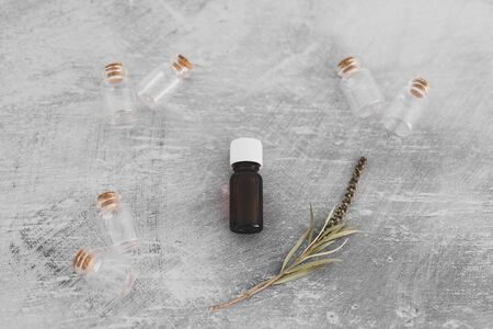 natural beauty and wellness concept, essential oil bottle with tiny branch of leaves and other bottles in the background shot at shallow depth of field Banco de Imagens - 133303835