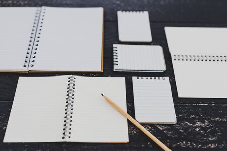 looking for ideas or starting a new project conceptual still-life, group of different notepad and notebooks opened up on desk with blank pages creating a geometric pattern