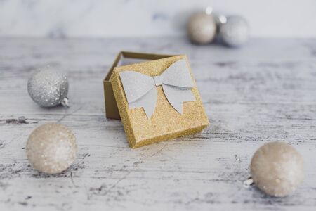 Christmas gift box with baubles around it wth gold and silver colors on wooden desk, edited with light and airy tones Stok Fotoğraf