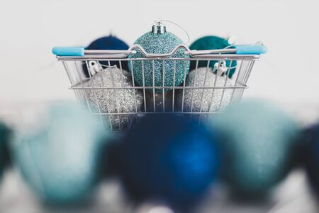 festive shopping and decorations conceptual still-life, Christmas baubles in shopping basket with blue and silvery tones shot at shallow depth of field