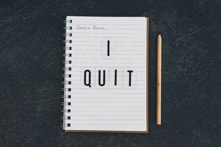 leaving a corporate job conceptual still-life, dear boss I quit message on notebook