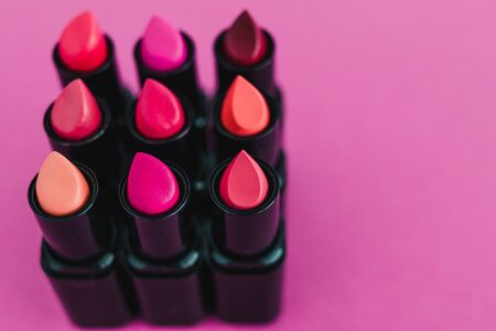 make-up and beauty industry still-life with group of colorful lipsticks in square composition on pink background from 45 degree angle