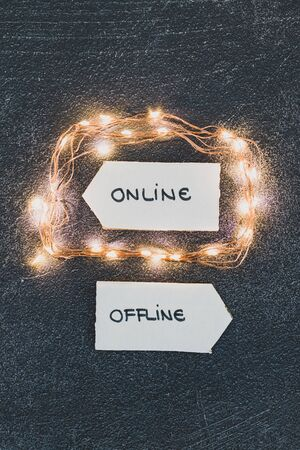 social media lifestyle and stress of an hyperconnected world conceptual still-life, Online and Offline alternatives on signs pointing at opposite directions and led lights emphasizing the Online option Banco de Imagens