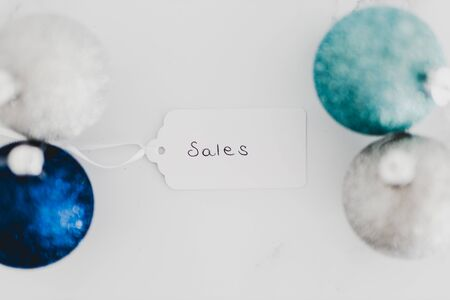 festive season shopping and promotions conceptual still-life, Sales price tag with blue and silver Chirstmas baubles on marble desk shot at shallow depth of field Stock Photo