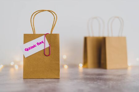 free samples and gifting conceptual still-life, shopping bag with price tag with Goodie Bag text on it and other bags in the background shot at shallow depth of field with bokeh and fairy lights