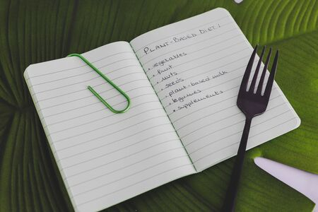 plant-based diet conceptual still-life, green notebook with food category list on tropical leaf with fork