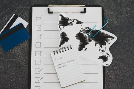 business going global conceptual still-life, world map and Conquering Global Markets to do list on clipboard