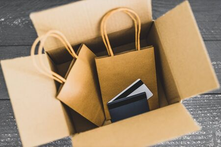 online orders conceptual still-life, shopping bags inside open delivery parcel with payment cards on top