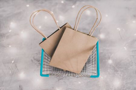 marketing promotions and customer purchasing habits conceptual still-life, shopping basket from topdown perspective with store bags in it