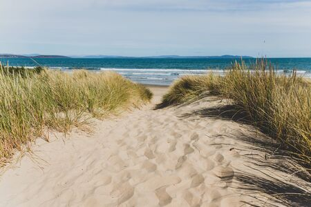 sand and grass path leading to Seven Mile Beach in Tasmania, Australia on late spring day with no people and partly cloudy weather Stock Photo