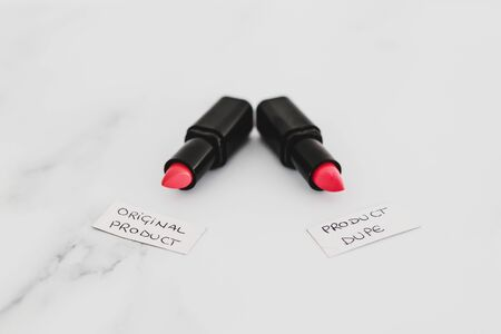beauty industry competition conceptual still-life, two identhical looking lipsticks with Original Product and Product Dupe labels