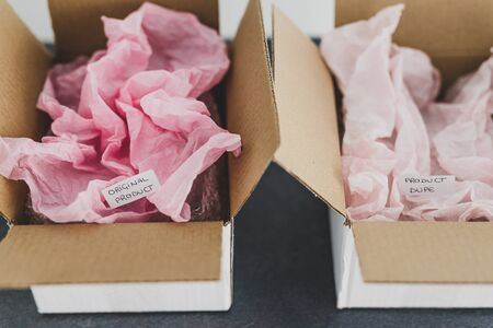 original product vs dupe imitation label inside delivery parcel boxes from online purchaseswith similar color paper, concept of competition and knock-off items