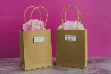 original product vs dupe imitation conceptual still-life, shopping bags with labels side by side with similar paper color symbol of cheap product alternatives  Stock Photo