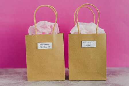 original product vs dupe imitation conceptual still-life, shopping bags with labels side by side with similar paper color symbol of cheap product alternatives  스톡 콘텐츠
